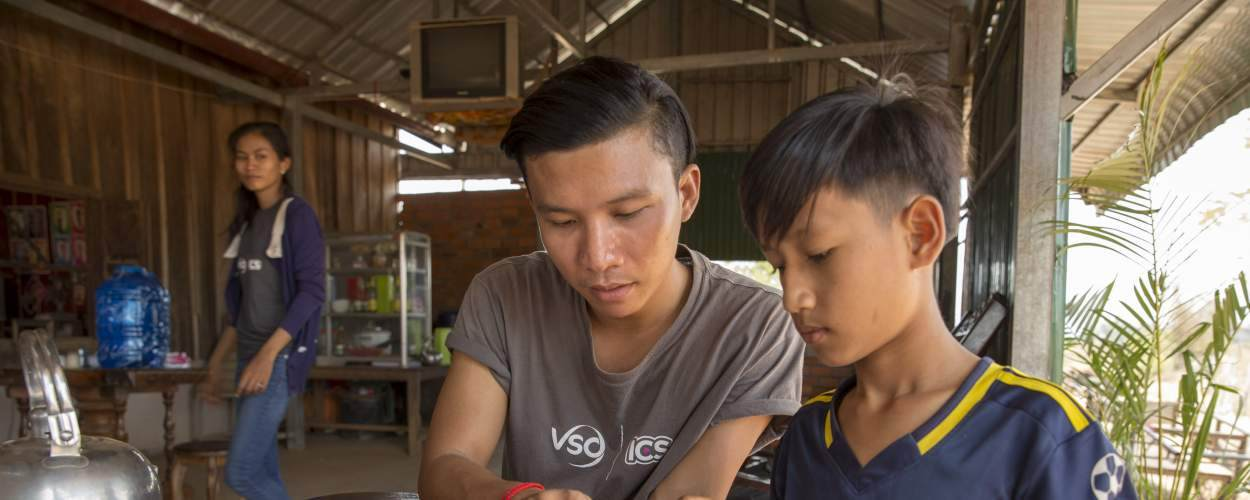 volunteer Ratha Chea helping a school child with his homework, Battambang, Cambodia