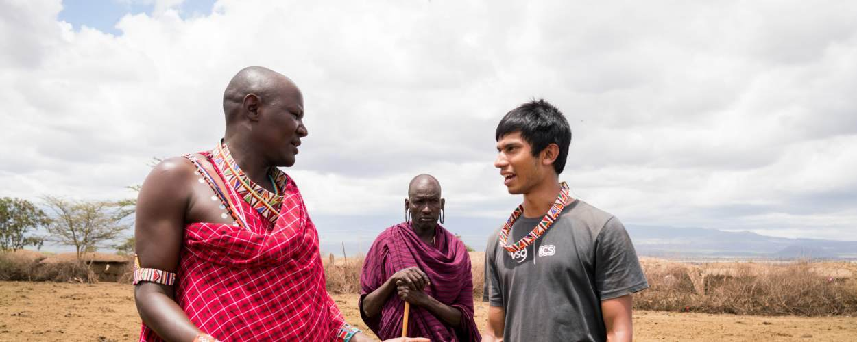 Volunteer Naseem Haque, 18, speaks with Maasai chief Benson Meoli